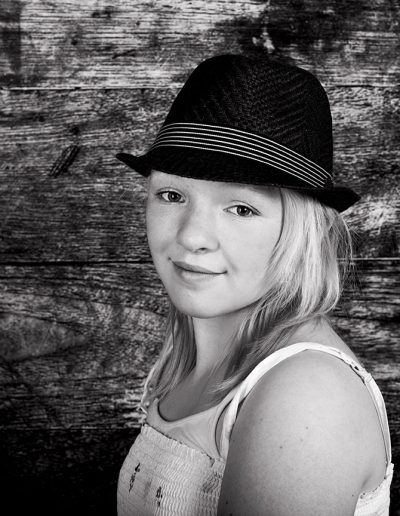 tween girl with hat black and white portrait